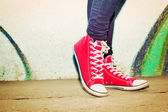 Close up of red sneakers worn by a teenager. — Stock Photo