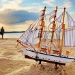 Ship model on summer beach at sunset — Stock Photo
