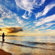Woman standing in ocean. Dramatic sunset sky — Stock Photo