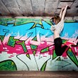 Stylish girl in a dance pose against graffiti wall — Stock Photo