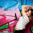 Stylish girl in a dance pose against graffiti wall — Stock Photo #31832467