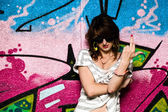 Stylish girl showing fuck off against graffiti wall — Foto Stock