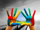 Painted colorful hands showing way to colorful happy life — Zdjęcie stockowe