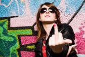 Stylish girl showing fuck off against graffiti wall — Stock Photo