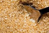 Brown, unrefined sugar and a silver spoon in it — Stock Photo