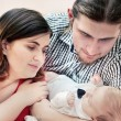Stock Photo: Mother and father with their young baby. Happy young family portrait.