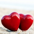 Two red hearts on the beach symbolizing love, Valentine's Day, romantic couple — Stock Photo