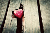Red heart in crack of wooden plank. Symbol of love — Stock Photo