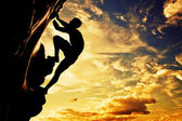 A silhouette of man free climbing on rock — Stock Photo