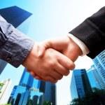 Business handshake, skyscrapers background — Stock Photo