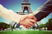 Рandshake on Eiffel Tower background — Stock Photo