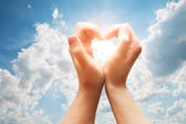 Man and woman hands make a heart on blue sunny sky — Stock Photo