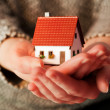 Woman holding a small new house in her hands — Stock Photo #45580539