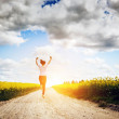 Woman running and jumping for joy towards sun — Stock Photo #48611731