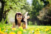 Woman lying on grass full of spring flowers and smiling. — Stock Photo