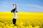Happy young woman on spring field. — Stock Photo