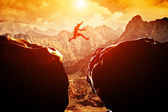 Man jumping over precipice — Stockfoto