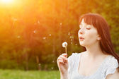 Woman blowing a dandelion — Stock Photo