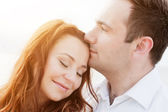 Young happy couple in love. Romantic moment on the beach in sunshine — Stock fotografie