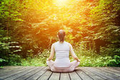 Woman meditating in a forest — Stockfoto