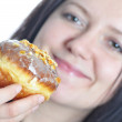 Portrait of a young woman eating a donut — Stock Photo #16191569