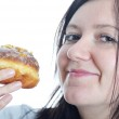 Portrait of a young woman eating a donut — Stock Photo #16191583