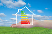 House and energy efficiency graph on hand — Stock Photo