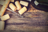 Bottle of white wine, corkscrew and corks on wooden table. — Stock Photo