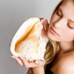 Glamour portret van mooie blonde vrouw model met dagelijkse make-up en gezond haar. mode glanzende markeerstift op huid en sexy glans lippen make-up. meisje met zeeschelp — Stockfoto