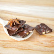 Delicious close-up of chopped chocolate on the wooden spoon — Stock Photo