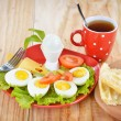Breakfast with hard boiled eggs, sliced in halves, cup of tea, salad, tomatoes, cheese and bread on the red plate and wooden background — Stok fotoğraf