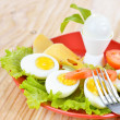 Breakfast with hard boiled eggs, sliced in halves, salad, tomatoes and cheese on the red plate and wooden background — Stock Photo