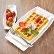 Breakfast dessert - golden waffles with ice cream and fresh sliced strawberries sprinkled with sugar and chocolate — Stock Photo
