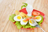 Breakfast with hard boiled eggs, sliced in halves, salad, tomatoes, cheese and bread on the red plate and wooden background — Stock Photo