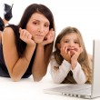Mother teaching her daughter how to use laptop — Stock Photo