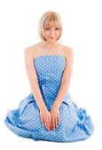 Sitting woman in blue polka dot dress — Stock Photo