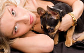 Lying blond woman is holding her chihuahua doggie — Stock Photo