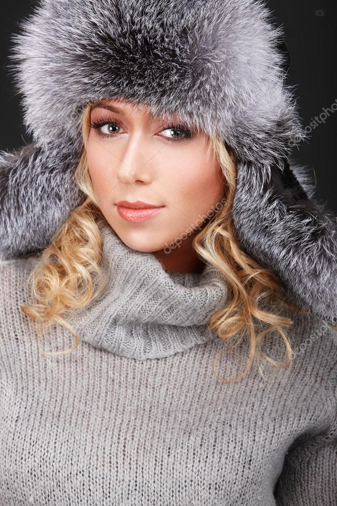 Portrait of young girl in fur hat and grey sweater — Stock Photo #19269189