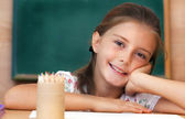 Schoolgirl in the clasroom - back to school — Stock Photo