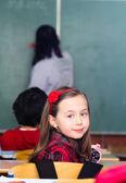 Happy little girl in school with her friends arround — Stock Photo