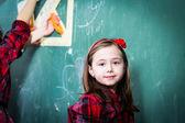 Pretty little girl standing in front of blackboard — Foto Stock