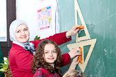 Teacher and schoolgirl in classroom — Stock Photo