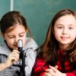 Two schoolgirls have a practice with microscope — Stock Photo