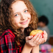 Happy little schoolgirl with apple  - portrait in classroom — Stock Photo