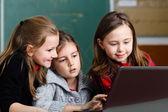 Schoolgirls working with laptop in classroom — Stock Photo