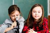 Dvě školačky má praxi s mikroskopem — Stock fotografie