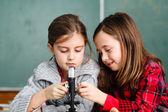 Zwei schülerinnen haben eine praxis mit mikroskop — Stockfoto