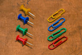 Colorful paper clips set on old paper background — Stock Photo