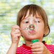 Beautiful little  girl blowing soap bubbles indoor — Stock Photo
