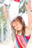 Happy little girl enjoying in summer day and playing with water — Stock Photo